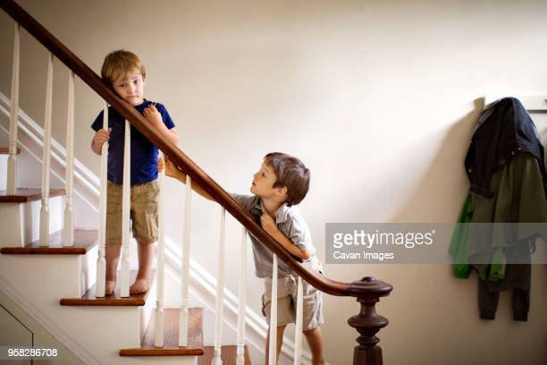 brothers standing at railing of staircase in house - garde corps photos et images de collection