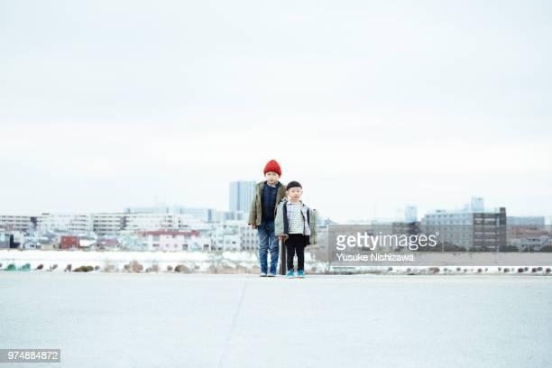brothers standing side by side - yusuke nishizawa stock-fotos und bilder