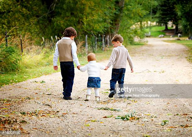 Brothers take little sister for a walk