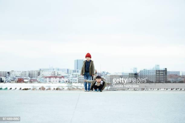 brothers taking a pose - yusuke nishizawa stock-fotos und bilder