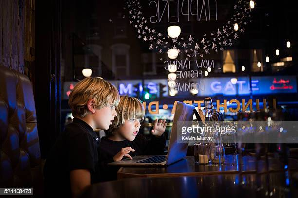 Brothers use laptop in cafe at night