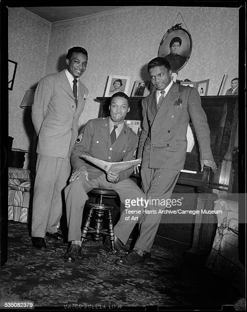 Brothers Walt Harper Ernie Harper wearing military uniform and Nate Harper posed in their home with piano and portrait photographs Pittsburgh...