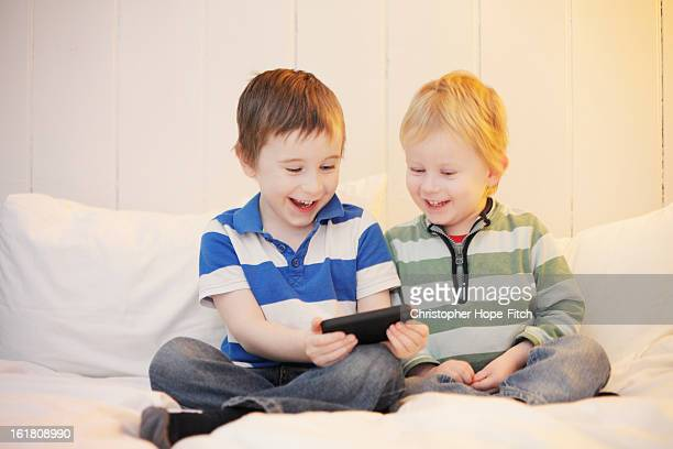 brothers watching a video - ボーダーシャツ ストックフォトと画像