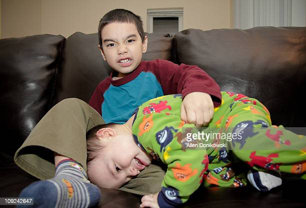 Brothers wrestling on the couch