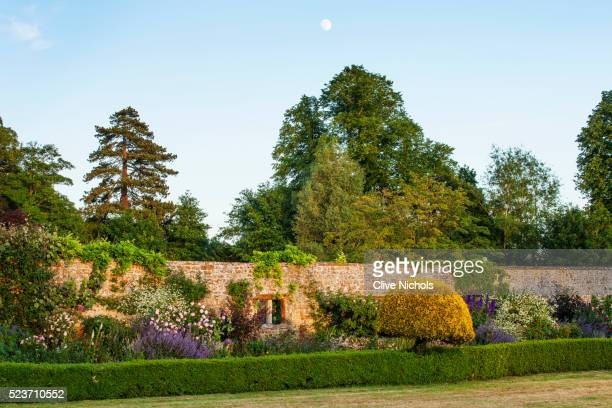 Broughton Castle, Oxfordshire: Border Beside The Walled Garden with Roses and Nepeta.. Flowers, Summ