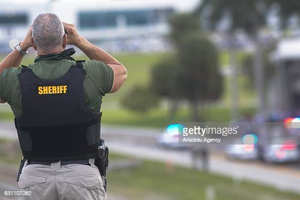 Broward County sheriffs deputy stands on a highway entering Fort Lauderdale International Airport using binoculars to look towards the airport on...