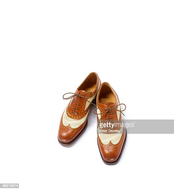 Brown and canvas brogues on white background.