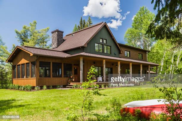 brown and green stained spruce wood country home with veranda, quebec, canada - facade stock pictures, royalty-free photos & images