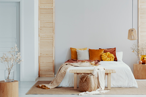 Brown and orange pillows on white bed in natural bedroom interior with wicker lamp and wooden bedside table with vase 1082907946