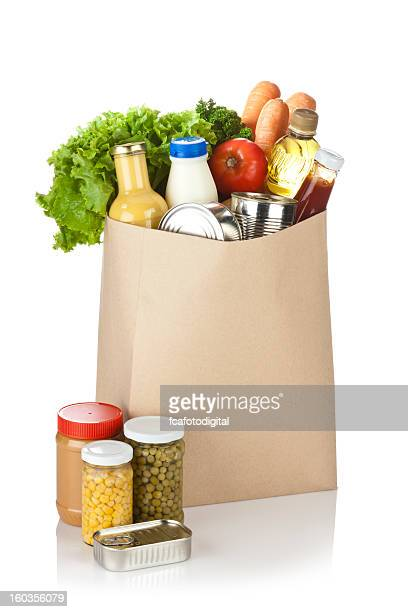 Brown bag full of groceries sits on white background