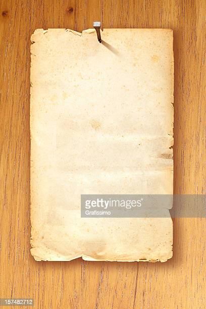 brown blank wanted poster fixed with nail on wooden background - old parchment background burnt stock photos and pictures