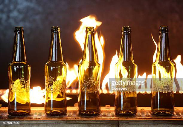 Brown bottles with the Baltika beer logo move along a conveyor belt past flames after shaping at the Ruscam Kirishi OJSC glass manufacturing plant in...