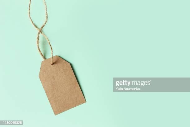 brown cardboard price tag on pastel green background, top view. sign sale. - precio fotografías e imágenes de stock