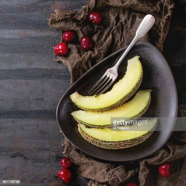 Brown ceramic plate with sliced melon served with cherry berries and vintage fork on wet sackcloth rag over old dark textured iron background Top...