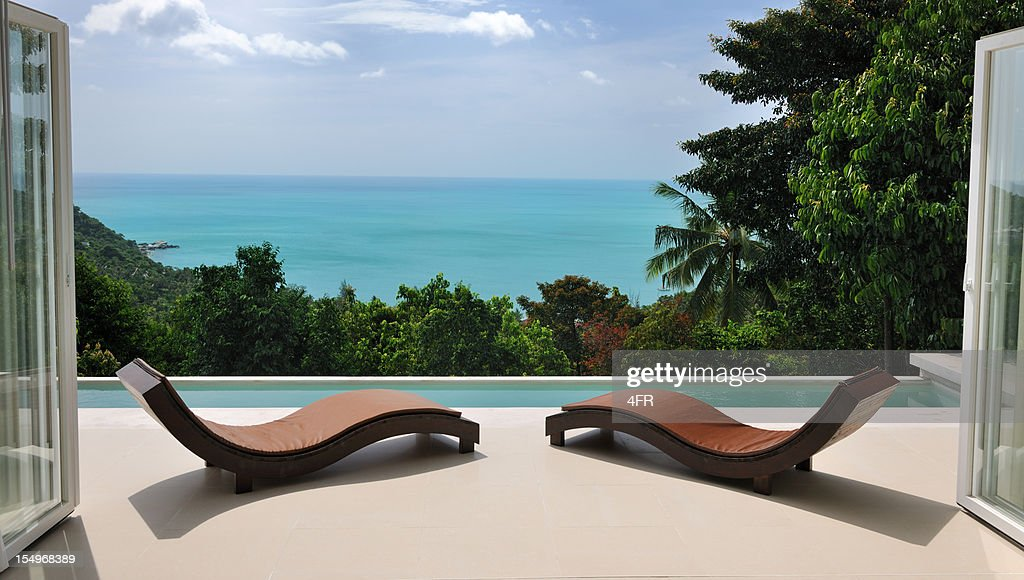 Brown chaises longues au bord de la piscine privée de la villa : Photo