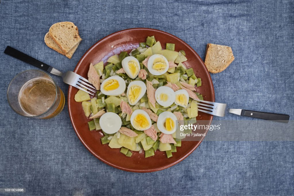 Brown clay plate with a potato and broad bean salad for two on a blue table with some bread and a glass of beer : Foto de stock