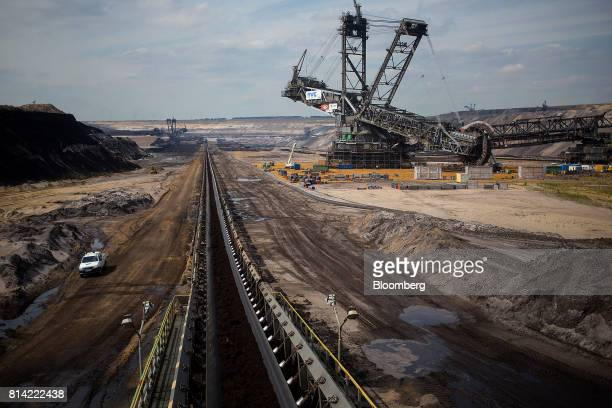 Brown coal passes along a conveyor belt as a giant excavator operates beyond at the Garzweiler open cast lignite mine operated by RWE AG in...