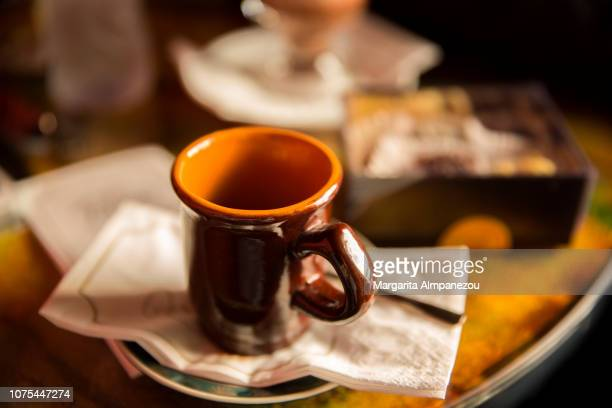 Brown coffee cup served on a table with sweets