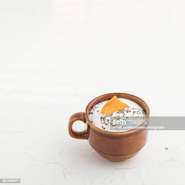 Brown cup with whipped cream, chia seeds and dried mango.