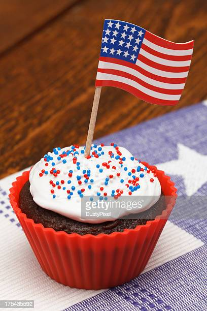 A brown cupcake has an American flag rising out of the icing