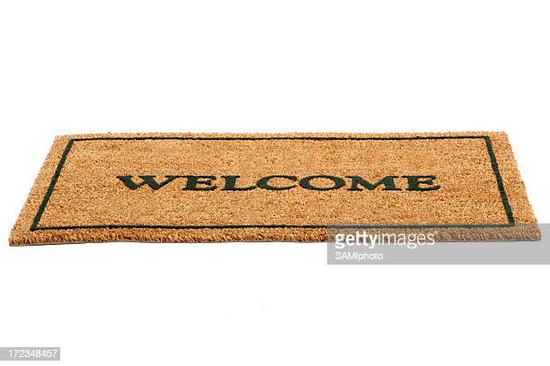 Brown door mat with welcome written across in black