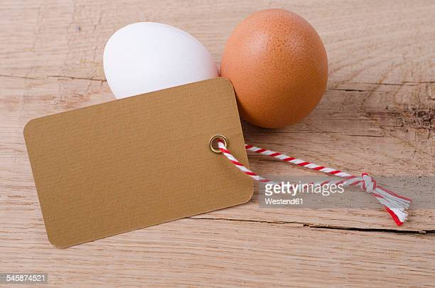 Brown egg, white egg and blank label on wood