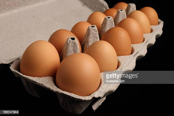 brown eggs in carton on black - dozen stock pictures, royalty-free photos & images