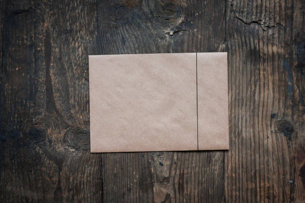 brown envelope on wooden background - brown envelope on the table stock pictures, royalty-free photos & images