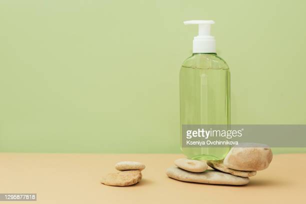 brown glass bottle with pump of cosmetic products on stone framed by green leaves of branches, beige background. natural organic spa cosmetic beauty concept. front view mock up. - pump dress shoe stock pictures, royalty-free photos & images