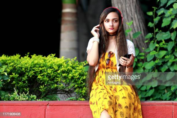 brown hair teenage girl enjoying music by headphone in the park - yellow dress stock pictures, royalty-free photos & images