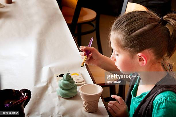 Brown Haired Girl Painting Pottery