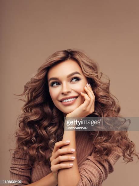 femme aux cheveux brune avec une coiffure frisée - brown hair photos et images de collection