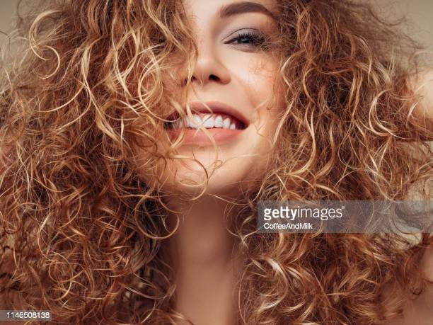 brown haired woman with voluminous hairstyle - curly stock pictures, royalty-free photos & images