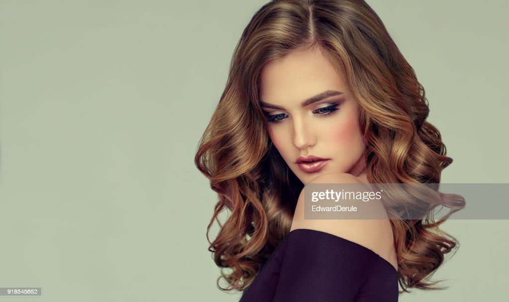 Brown haired woman with voluminous, shiny and curly hairstyle.Frizzy hair. : Stock Photo
