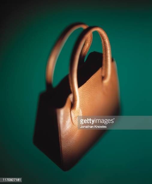 brown handbag on green background - brown purse stock pictures, royalty-free photos & images
