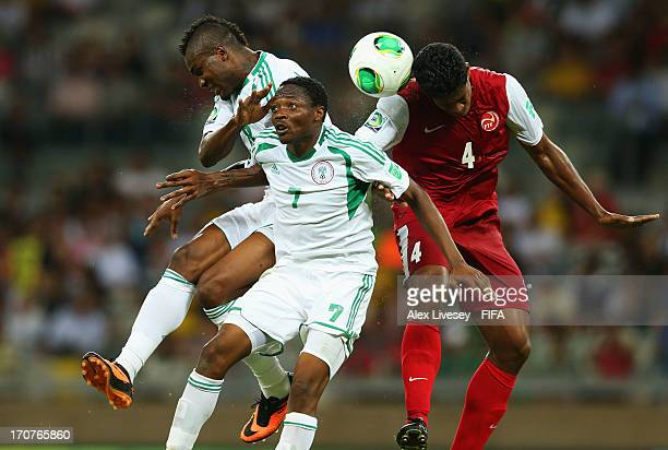 Brown Ideye and Ahmed Musa of Nigeria go up for a header with Teheivarii Ludivion of Tahiti during the FIFA Confederations Cup Brazil 2013 Group B...