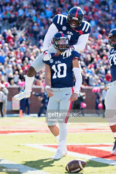 J Brown jumps on the back of Jordan Ta'amu of the Ole Miss Rebels in celebration after a touchdown in the first half past of a game the Arkansas...