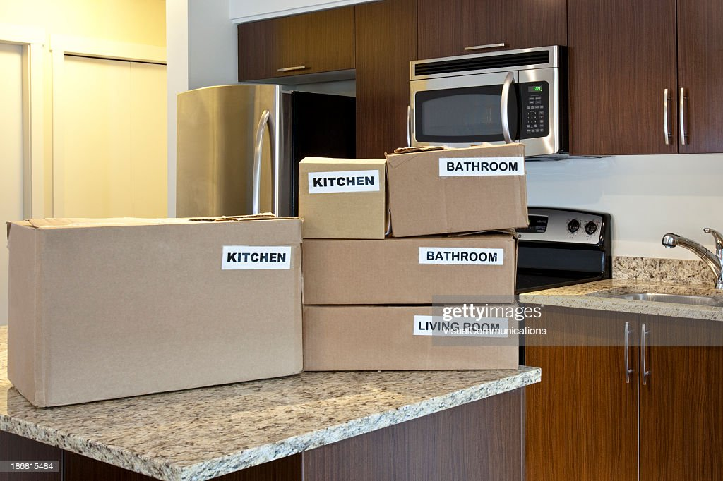 Brown Labeled Moving Bo Stacked On A Kitchen Island Stock Photo