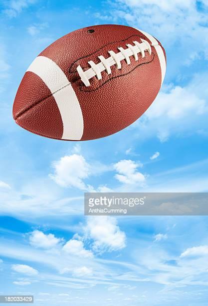 Brown leather american football midair in blue sky