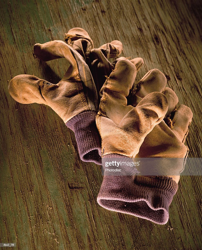 brown leather gloves lie on a wooden surface : Foto de stock