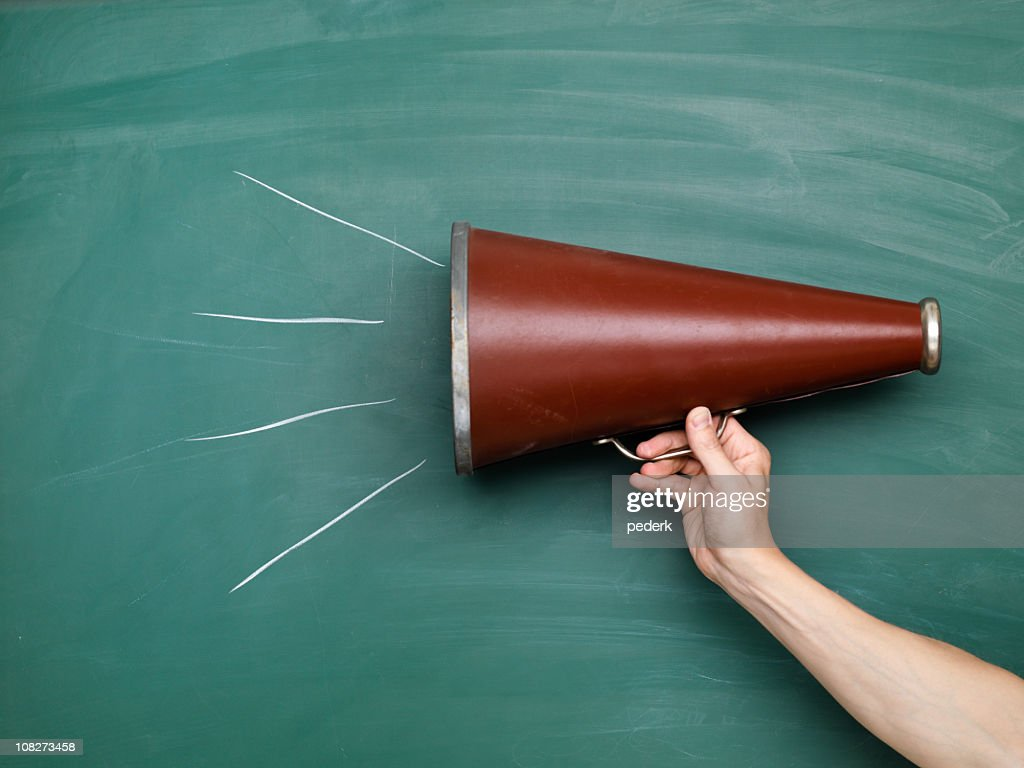 A brown megaphone in front of a green chalkboard with lines : Stock Photo