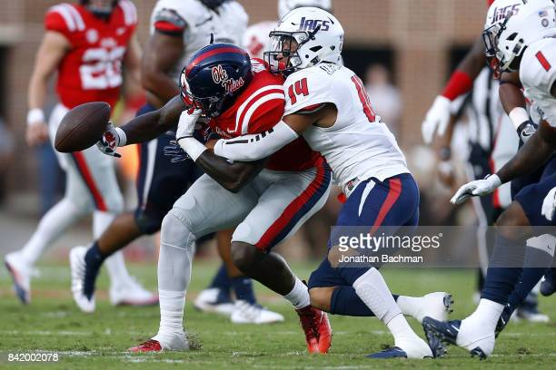 J Brown of the Mississippi Rebels catches the ball as Neiko Robinson of the South Alabama Jaguars defends during the first half of a game at...