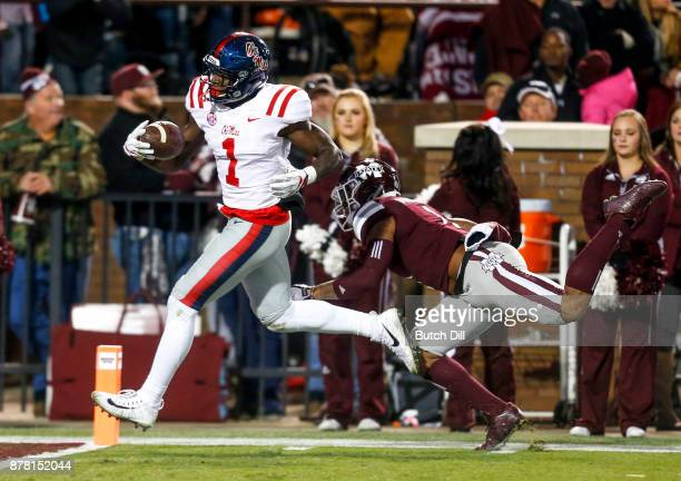 J Brown of the Mississippi Rebels scores a touchdown as Brandon Bryant of the Mississippi State Bulldogs tries to defend during the second half of an...