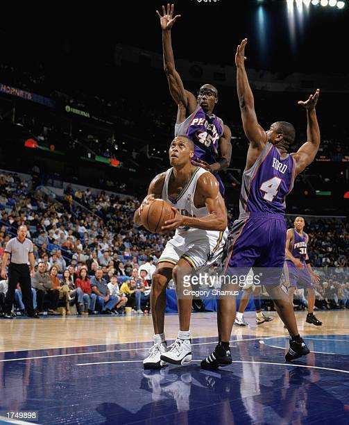 J Brown of the New Orleans Hornets covered by Bo Outlaw and Alton Ford of the Phoenix Suns goes to shoot during the game at New Orleans Arena on...
