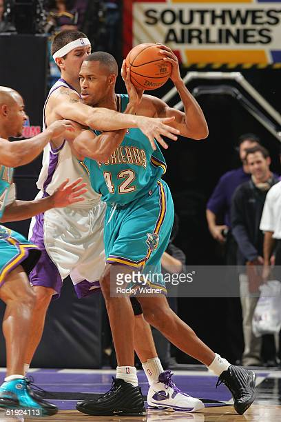 J Brown of the New Orleans Hornets is defended by Brad Miller of the Sacramento Kings during the game on December 19 2004 at Arco Arena in Sacramento...