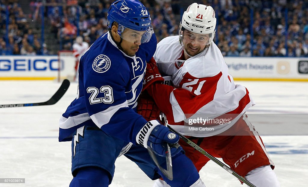 J.T. Brown #23 of the Tampa Bay Lightning and Tomas Tatar #21 of the Detroit Red Wings battle for the puck during the third period in Game One of the Eastern Conference Quarterfinals during the 2016 NHL Stanley Cup Playoffs at Amalie Arena on April 13, 2016 in Tampa, Florida.