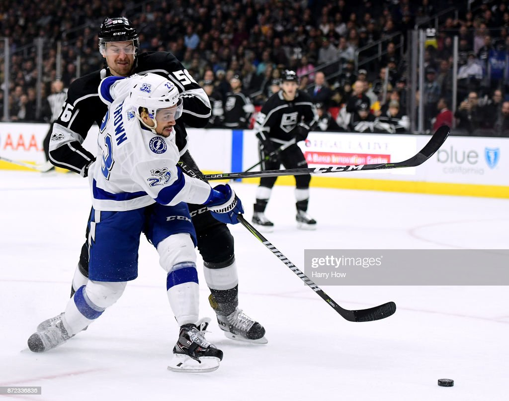 J.T. Brown #23 of the Tampa Bay Lightning attempts a shot as he is hit by Kurtis MacDermid #56 of the Los Angeles Kings during the first period at Staples Center on November 9, 2017 in Los Angeles, California.