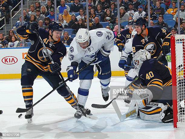 T Brown of the Tampa Bay Lightning is defended by Justin Falk Robin Lehner and Taylor Fedun of the Buffalo Sabres during an NHL game at the KeyBank...