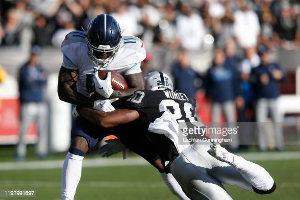 J Brown of the Tennessee Titans breaks a tackle by Daryl Worley and Erik Harris of the Oakland Raiders to score a touchdown in the second quarter at...