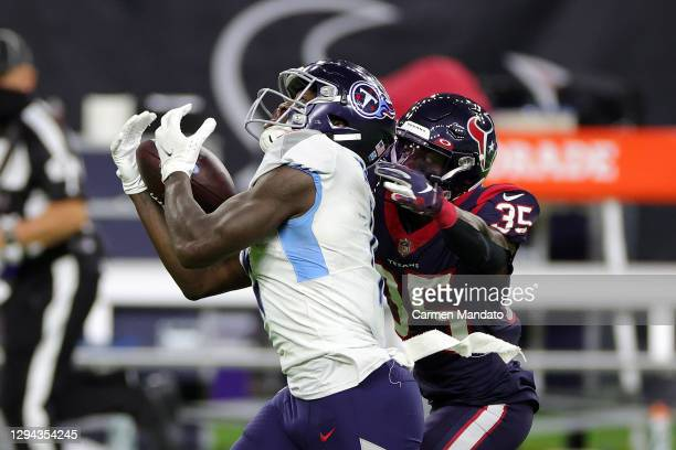Brown of the Tennessee Titans catches a pass in front of Keion Crossen of the Houston Texans during the second half of a game at NRG Stadium on...